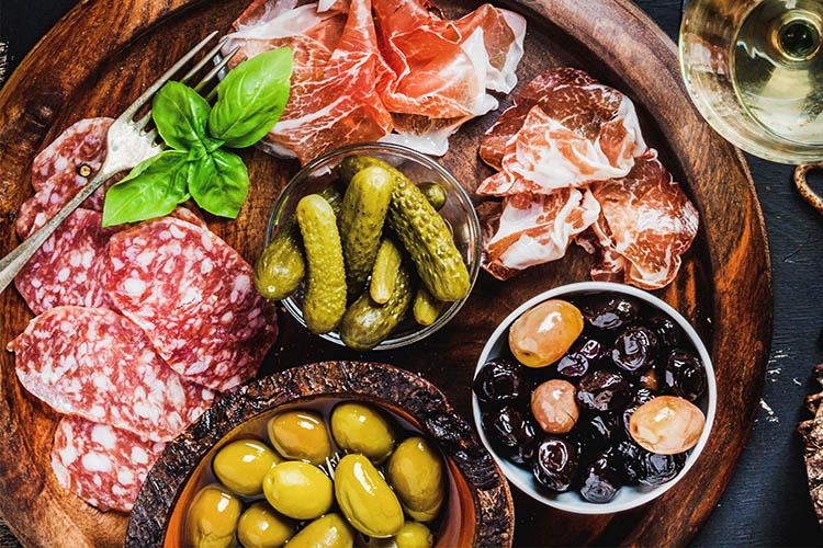 Zutaten für Raclette: Schinken, Gewürzgurken und Oliven